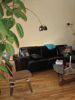 Photo of Noguchi Coffee Table with Leather Sectional and Eames Chair